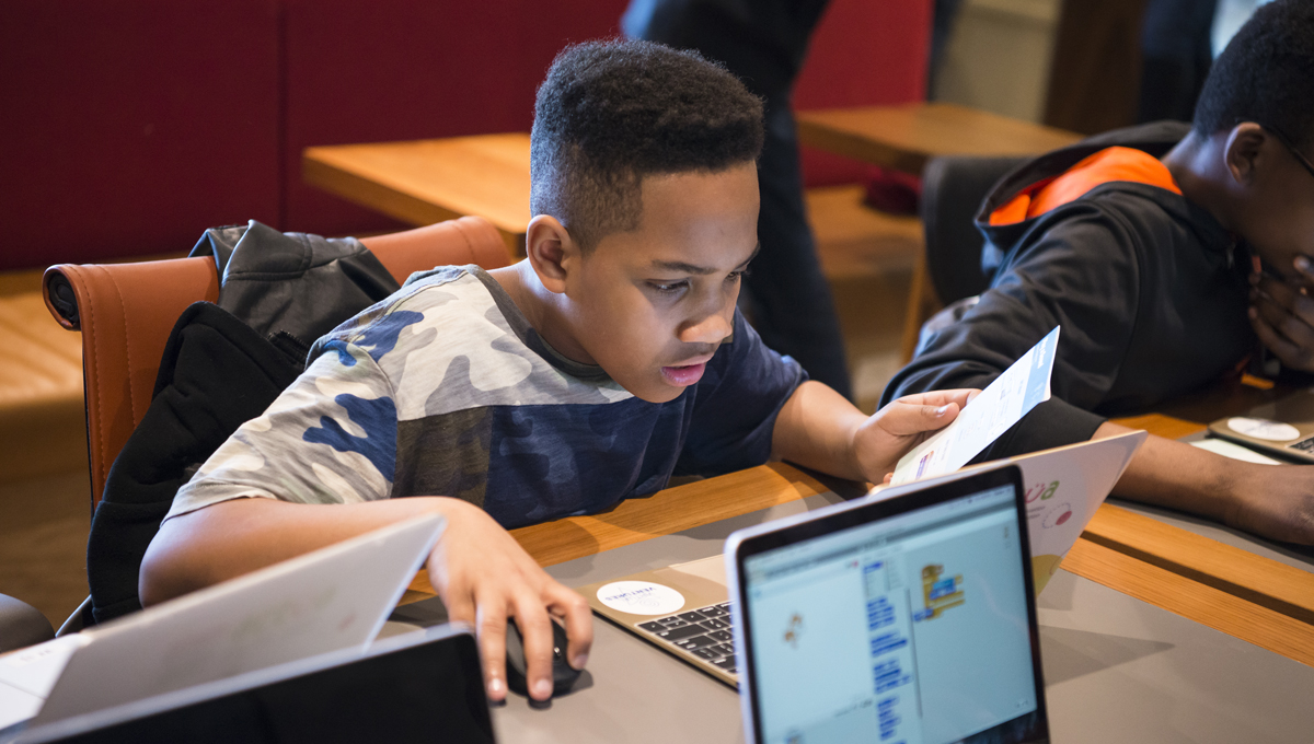 A collaboration between Carleton's Virtual Ventures, Shopify and the Boys and Girls Club of Ottawa. aims to create digital literacy programs for youth. Pictured: a boy learns about coding in front of a laptop.