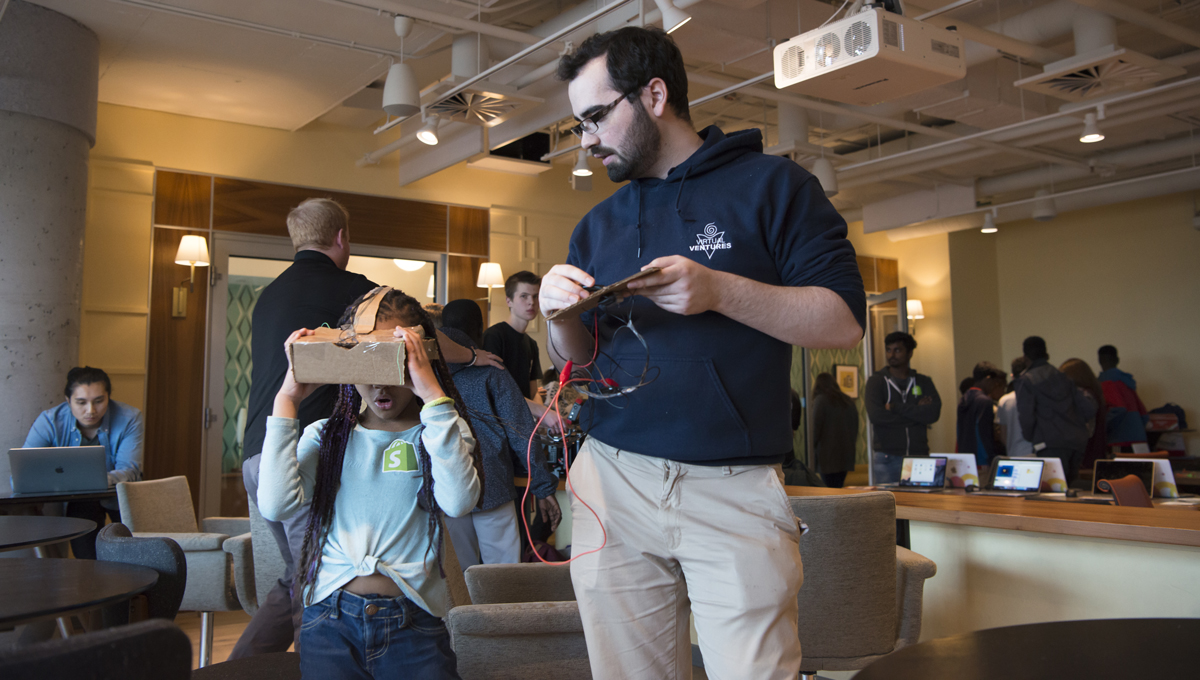 A collaboration between Carleton's Virtual Ventures, Shopify and the Boys and Girls Club of Ottawa. aims to create digital literacy programs for youth. Pictured: a girl learns about VR by experiencing Google Cardboard under the supervision of a Virtual Ventures staffer.