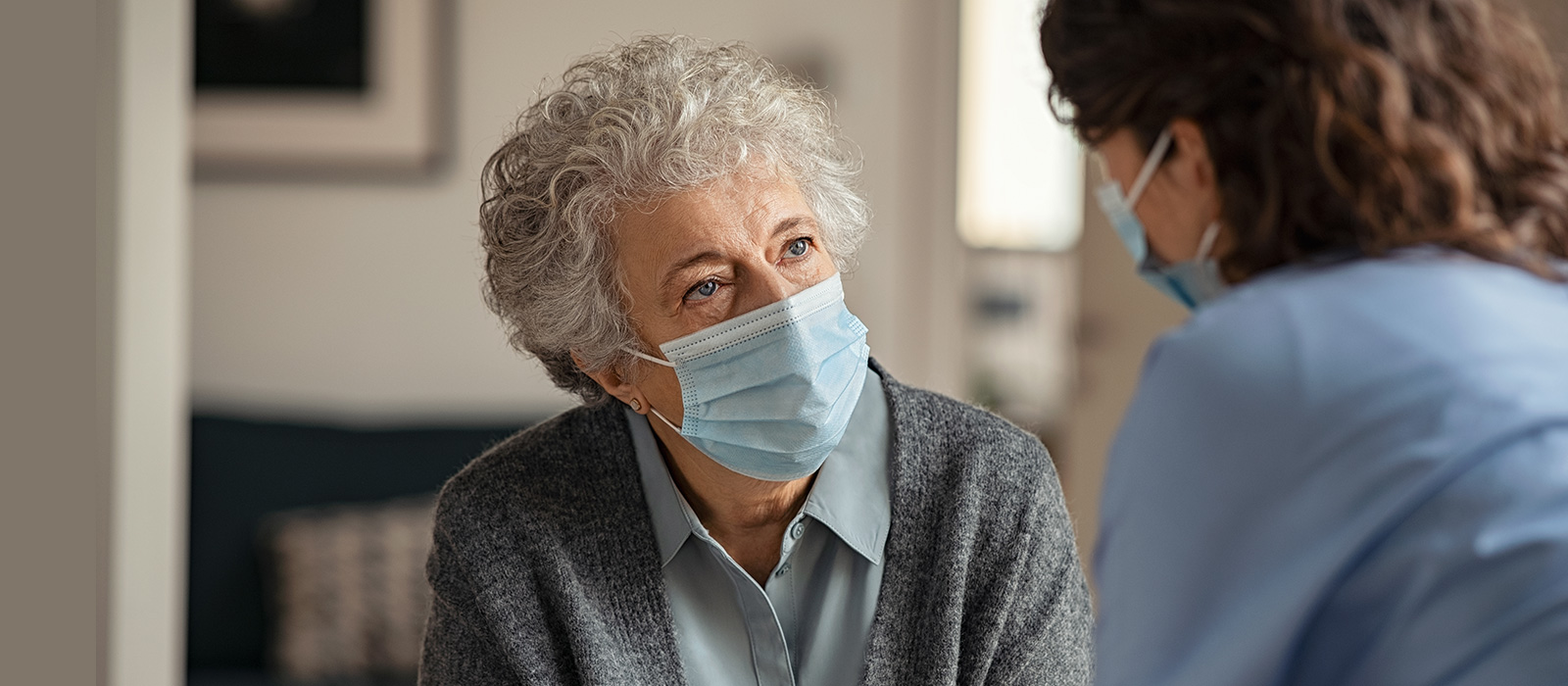 Elder woman wearing safety protective mask talking to a nurse