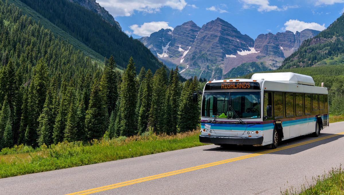 Shuttle bus on a mountain road in Maroon Bells Scenic Area in Aspen, Colorado.