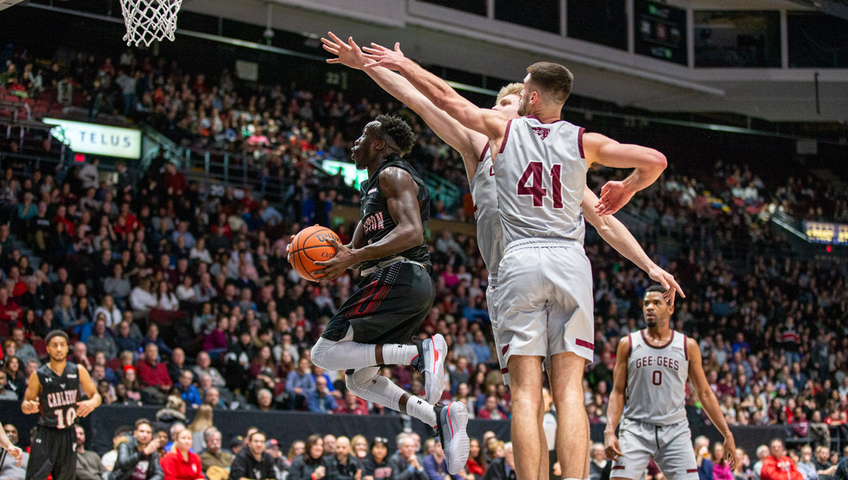 A Ravens men's basketball player goes to the basket against two uOttawa Gee Gees players.
