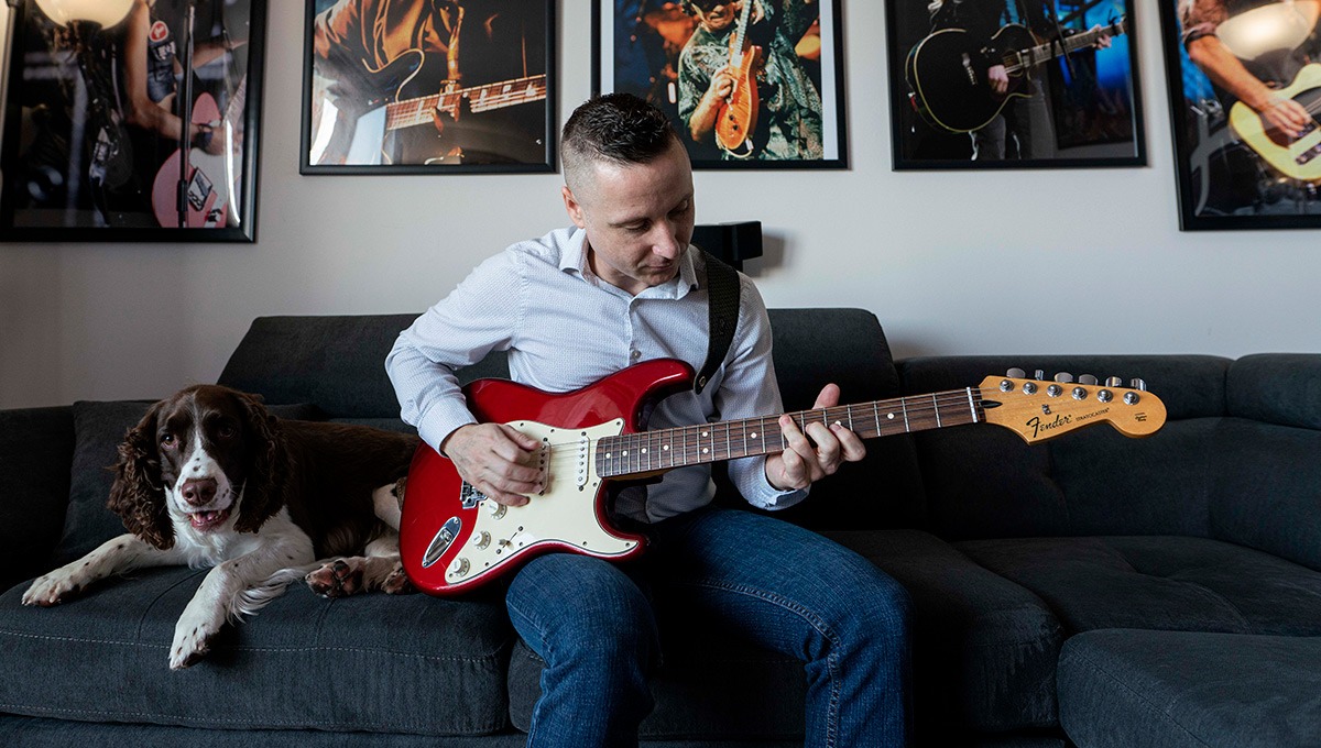Mickey Magennis plays guitar next to his dog