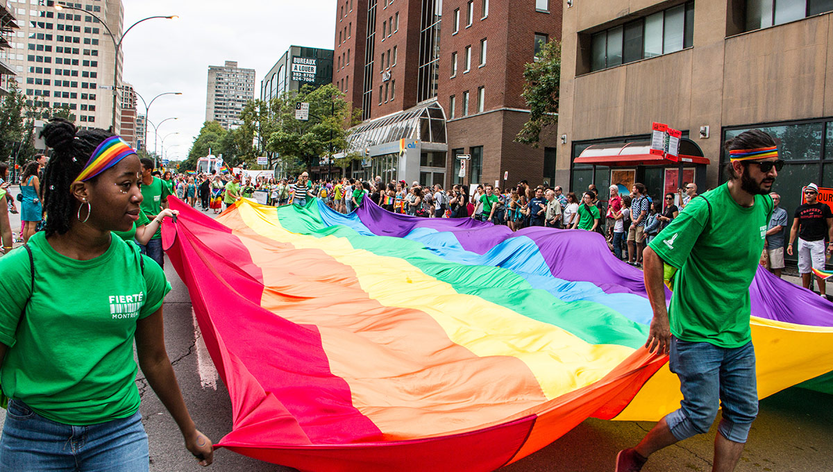 Volunteers wave a big rainbow flags during Montreal's Pride March in 2016