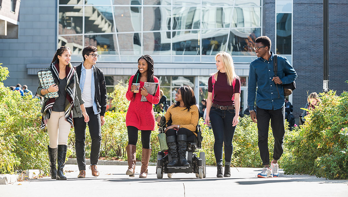 Group of Carleton University walking on campus; the student in the middle is using a wheelchair.