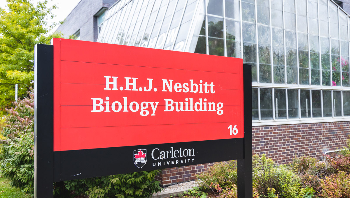 An close up of an exterior sign at the Nesbitt Biology Building on a cloudy fall day.