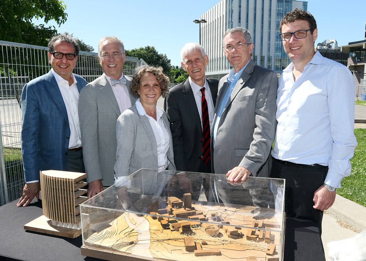 Stakeholders stand around a to-scale model of the new Sprott building on a sunny day.