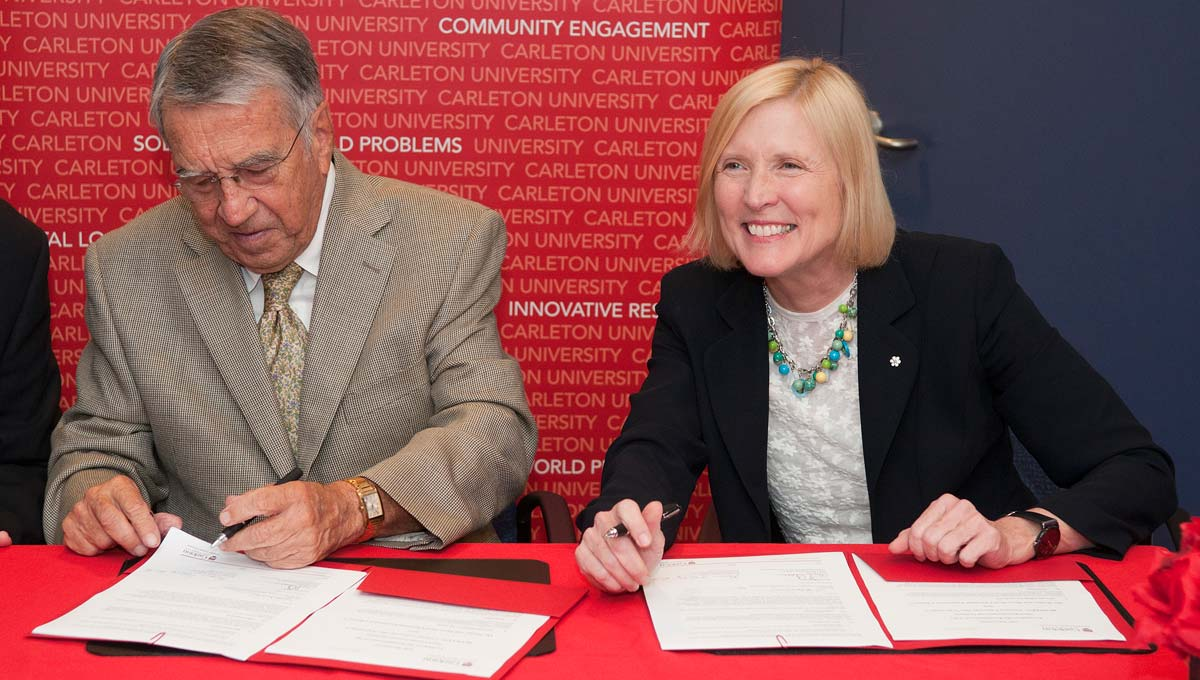 Wes Nicol and President Runte sign an agreement to kick off fundraising for the Sprott School of Business's new building.