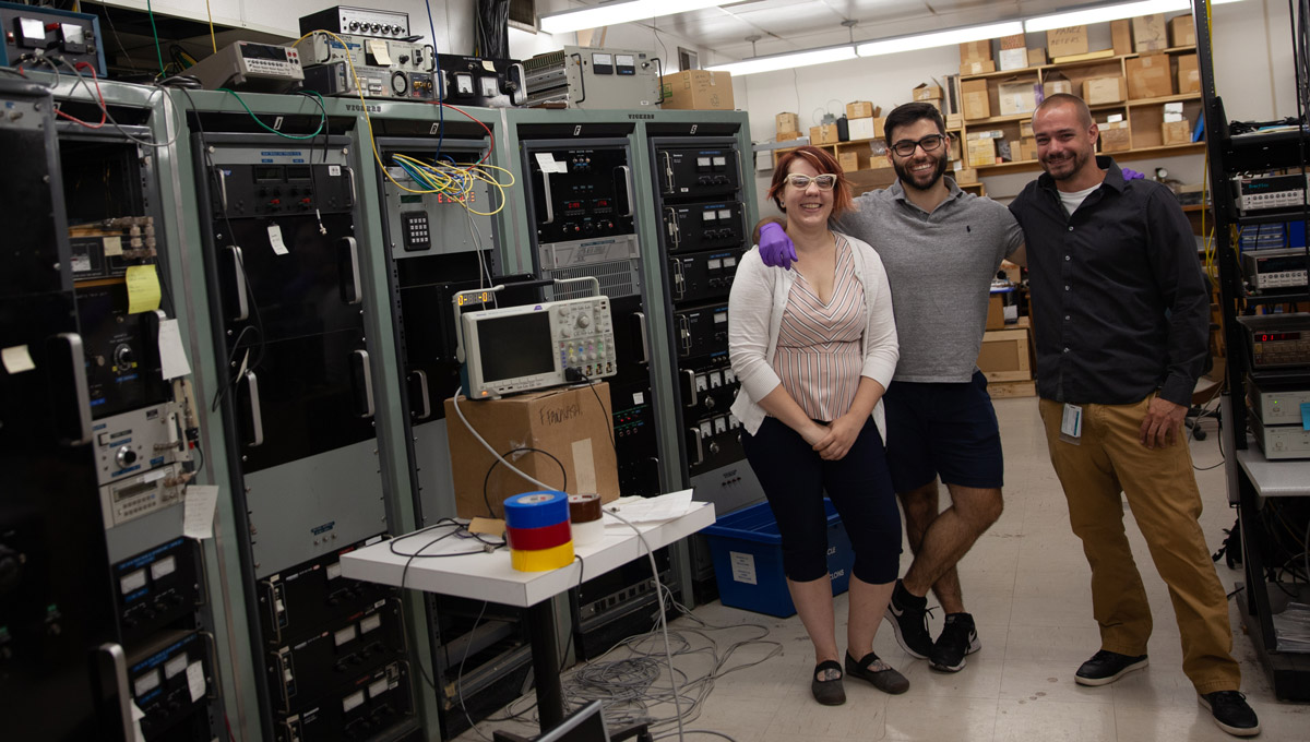 Members of the Ottawa Medical Physics Institute pose in a lab setting with arms over each others shoulders.