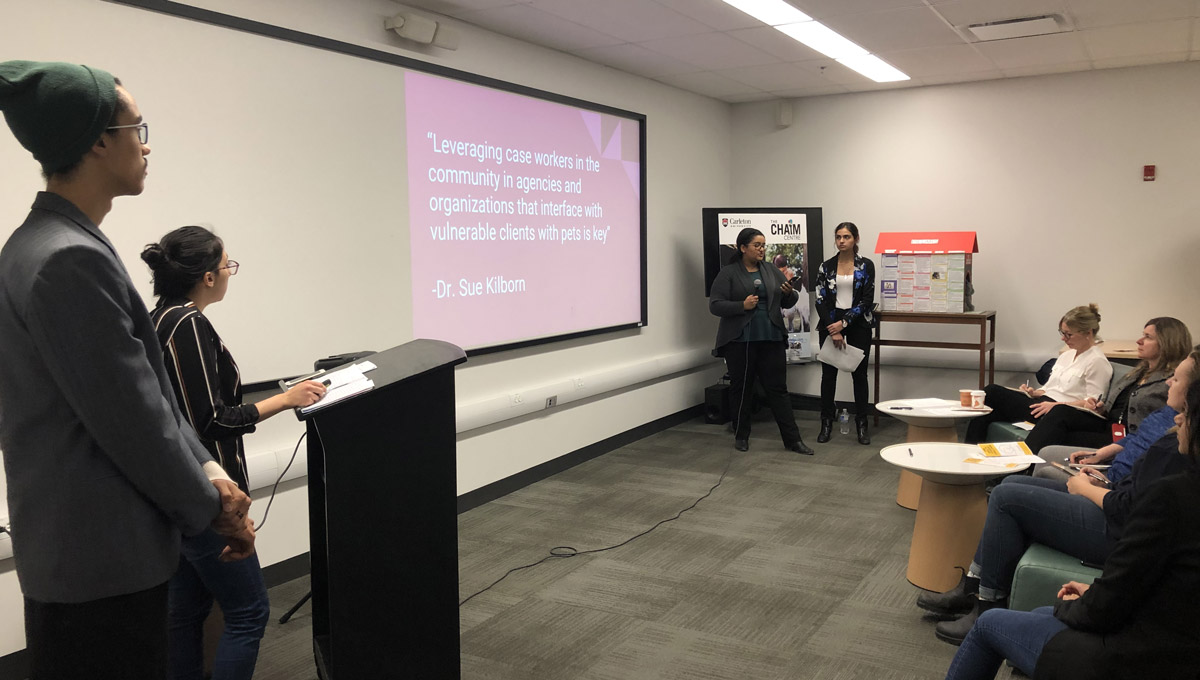 A projector displays a powrerpoint presentation while students speak to an audience in a conference room during the One Health Challenge.