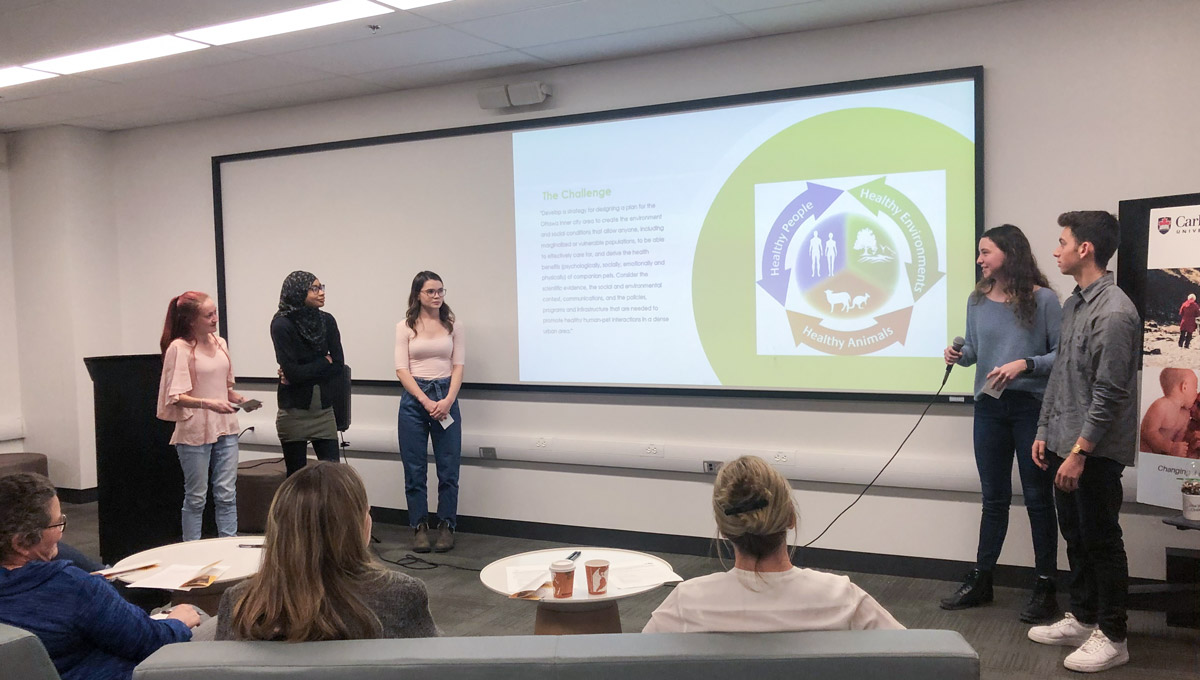 A students holds a microphone while delivering a presentation during the One Health Challenge, with her collegues looking on..