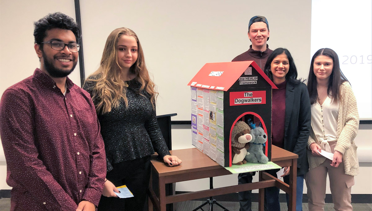 The winning group, called The Dogwalkers, pose while displaying a doghouse with messages written over it.