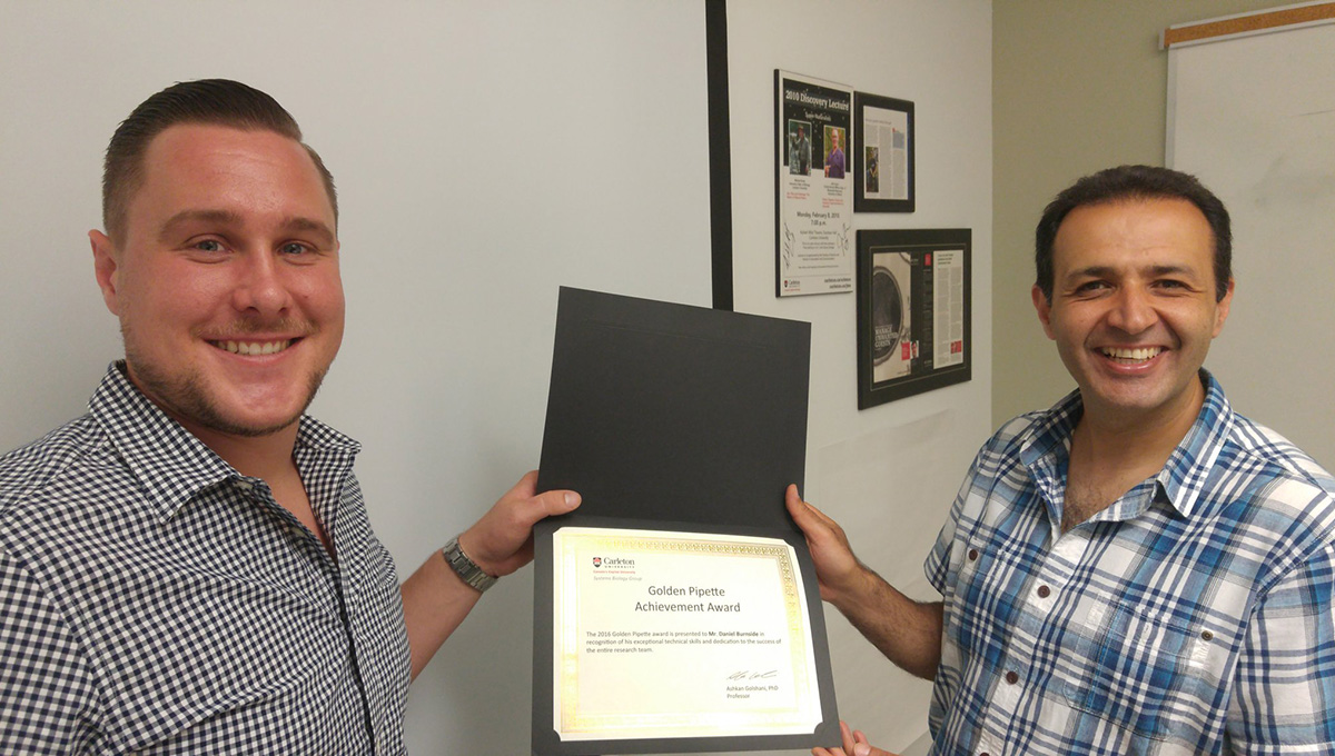 Prof. Ashkan Golshani (right) presents an award to a student in 2016