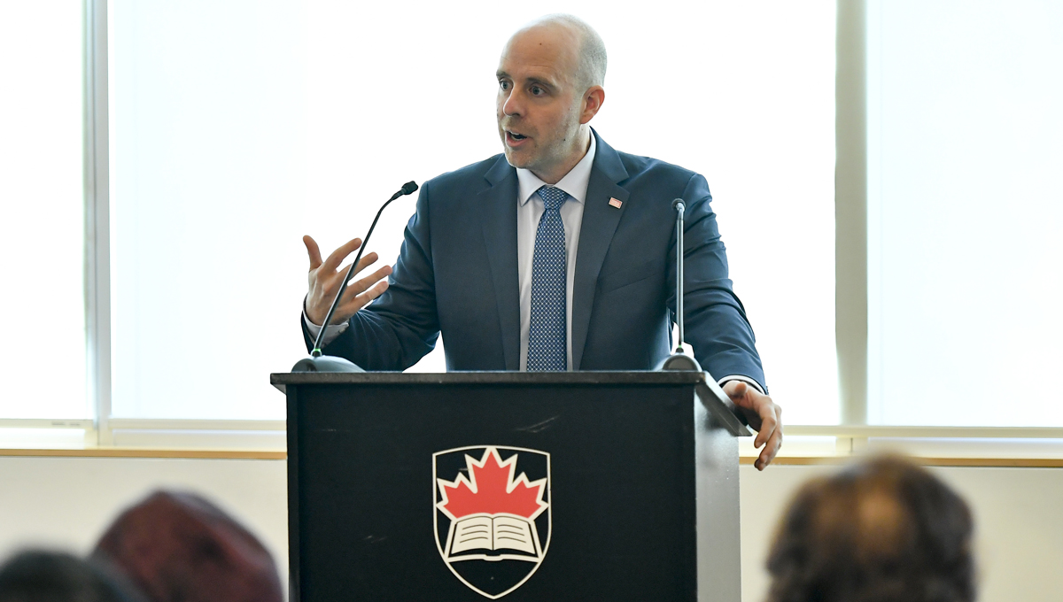Carleton President Benoit-Antoine Bacon speaks at a podium during the annual Orientation for Newly Arrived Diplomats in September 2018.