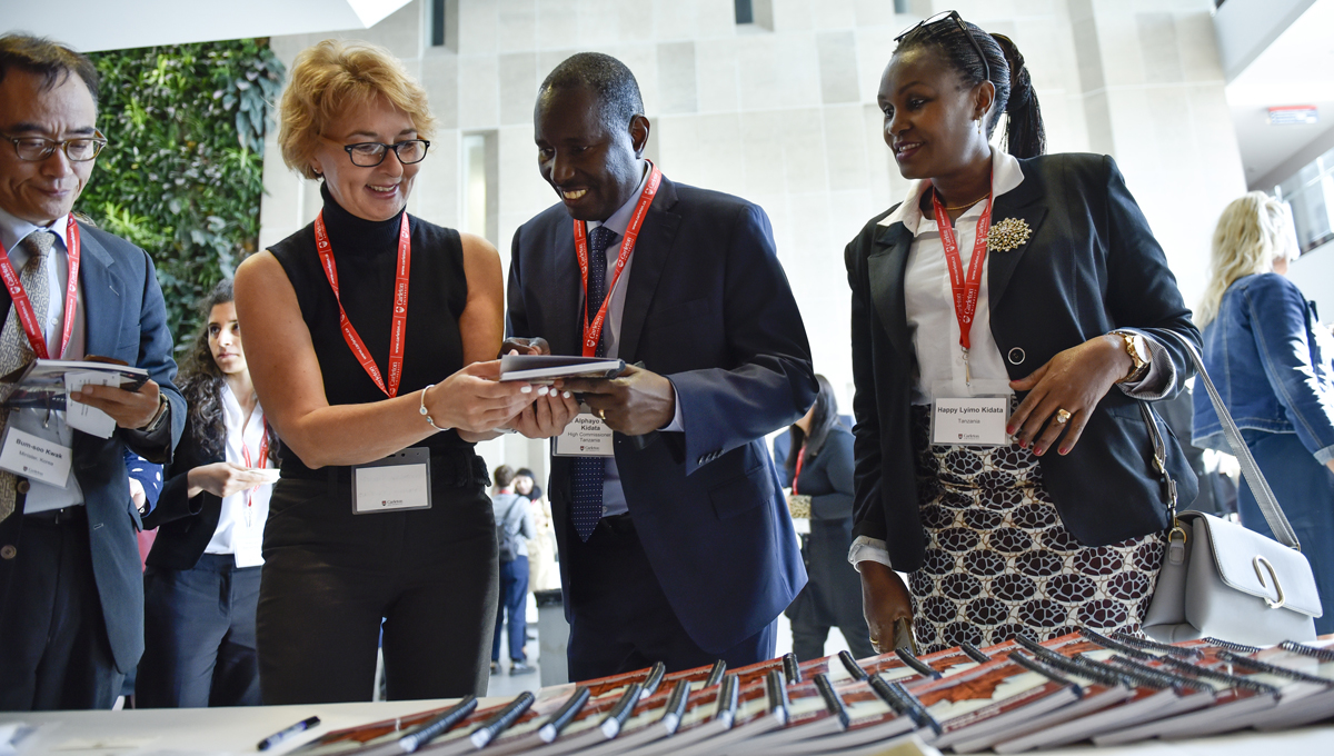 Diplomats connect and network as they gather printed programs during the annual Orientation for Newly Arrived Diplomats in September 2018.