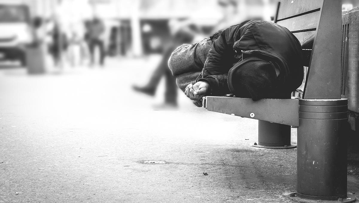 A homeless person sleeps on a sidewalk