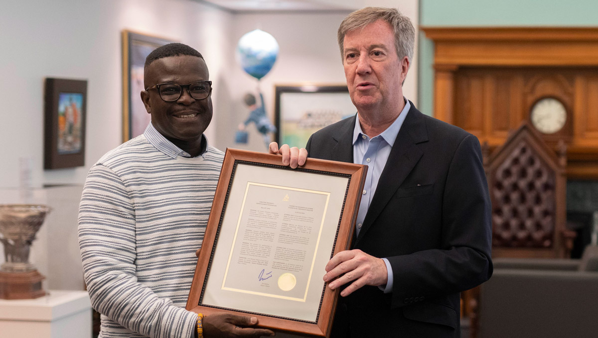 Mayor Jim Watson and a visiting Queen Elizabeth Scholarship- Advanced Scholars hold a framed proclamtion City Hall.
