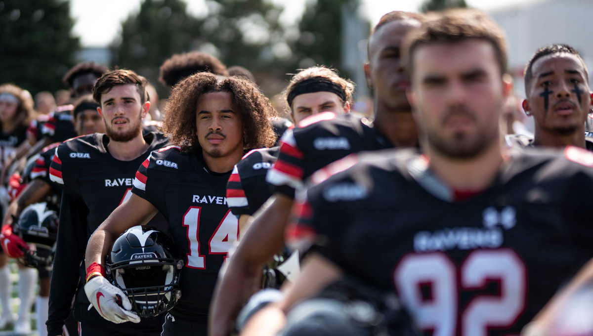 The 2019 Carleton Ravens stand ready for a game to begin while holding their helmets.