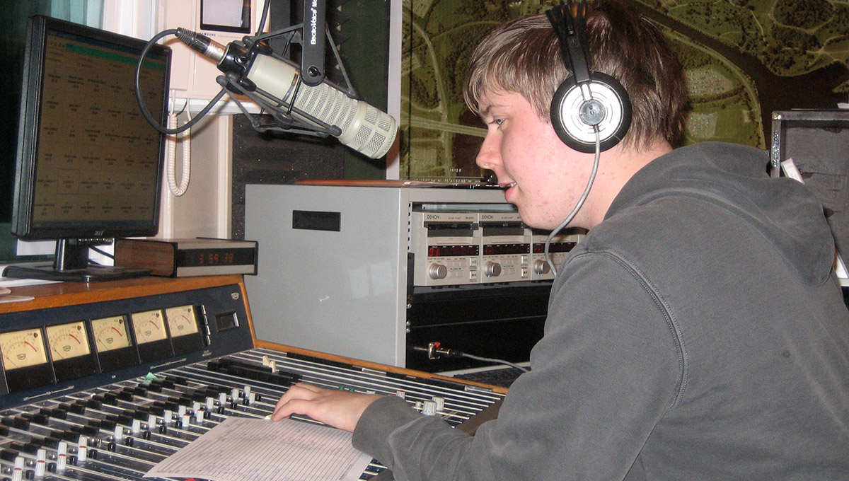 Photo of Nicholas Osborne with headphones on, sitting in a radio studio