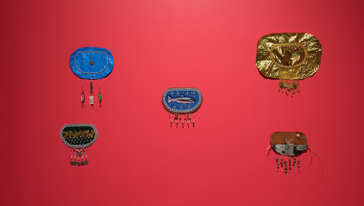 Five ovoid shapes are arranged on a red background. Each is made of different materials: blue tarp, gold foil, sealskin and reindeer leather, beading and patterned and stitched fabric. Each ovoid is embellished with an array of objects such as coins, tamarack cones or fishing lures suspended with thread along the bottom edge.