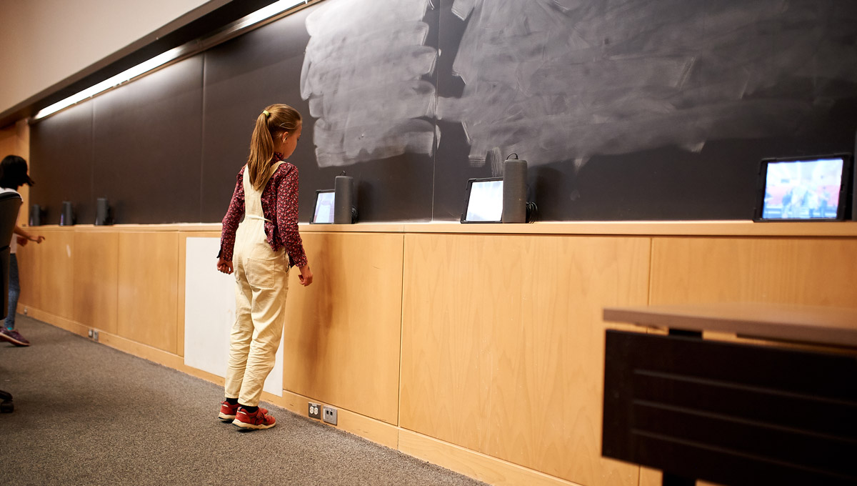 A child interacts with a music-making device positioned on a blackboard.