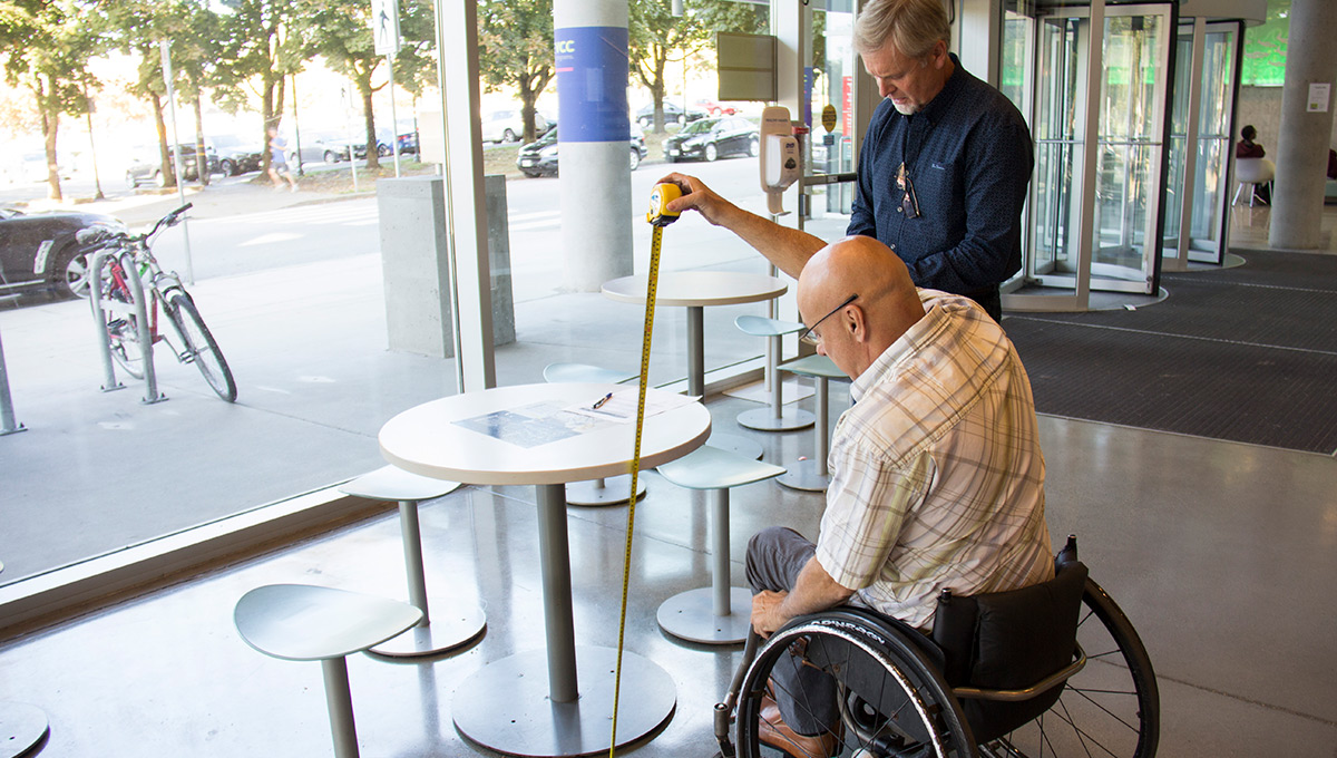 A person in a wheelchair and another man measure a table to meet Accessibility Certification rules.