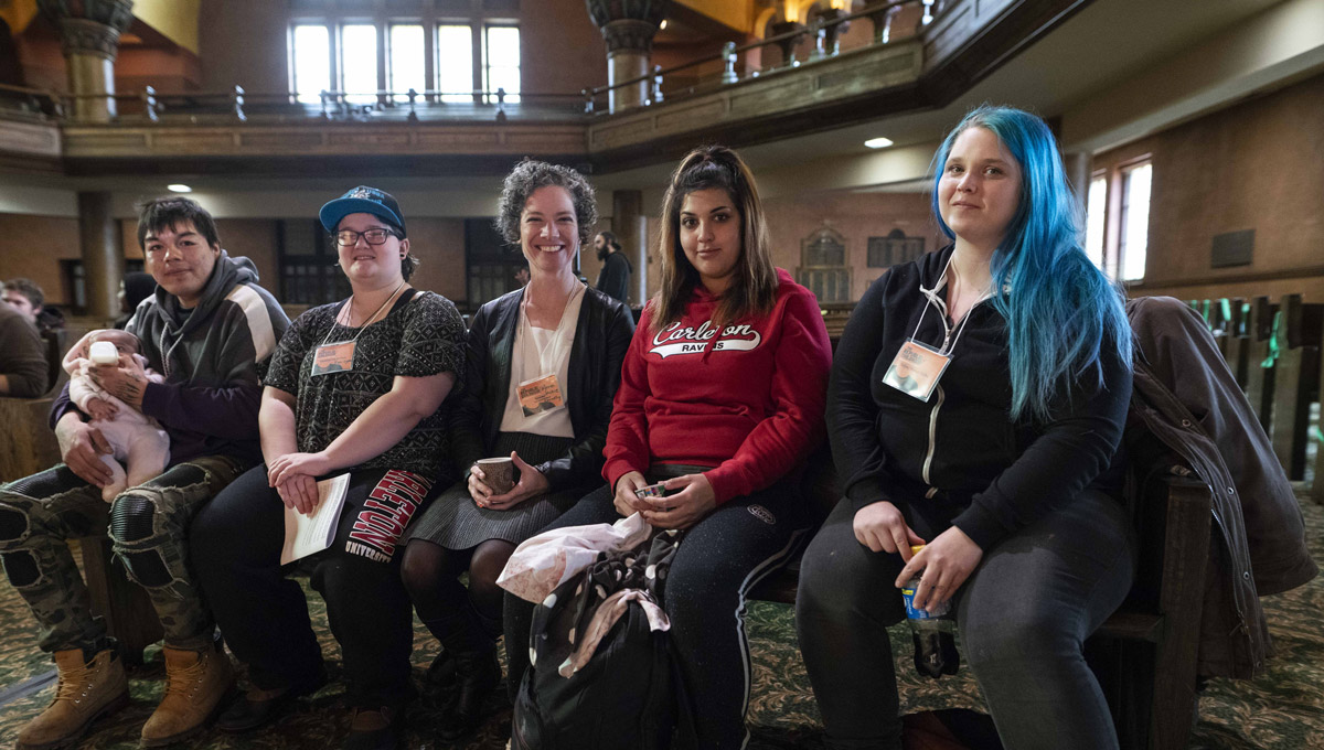 Joseph Mathias, Rae Lynne, Prof. Jacqueline Kennelly, Blanca Leanño, and Holly Petersen sit together on a pew in the Carleton Dominion-Chalmers Centre