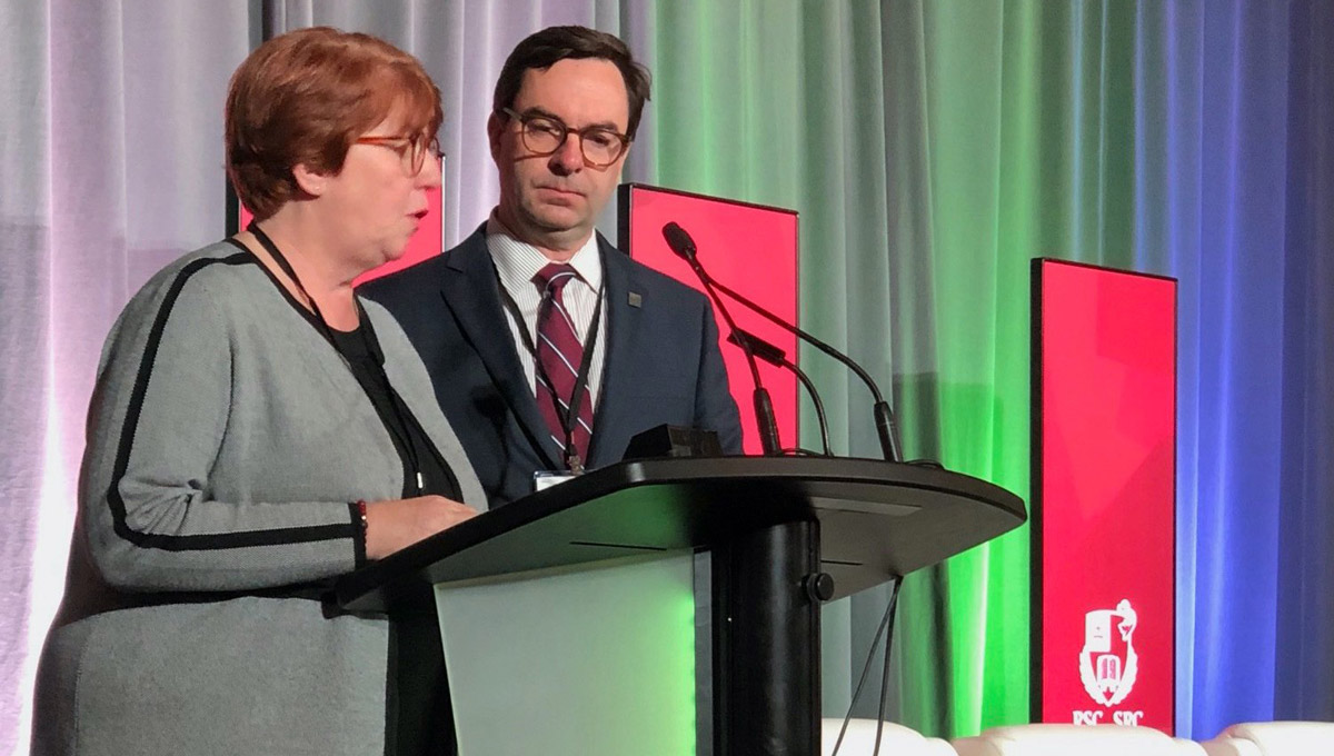 FASS Dean Pauline Rankin and a man in a suit speak at the podium during the Royal Society Celebration.