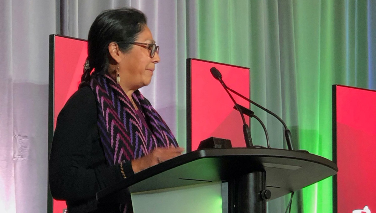 An woman in an Indigenous scarf speaks at the podium during the Royal Society Celebration.