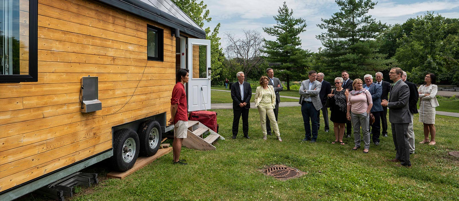 A small group tours outside the Northern Nomad tiny house, which overlooks the Rideau River near Richcraft Hall at Carleton University