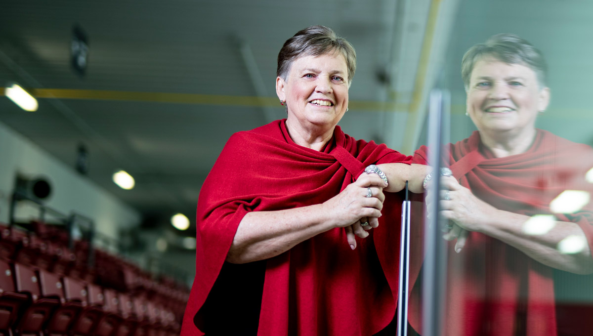 Shirley Mills leans against the glass hockey boards in a rink.