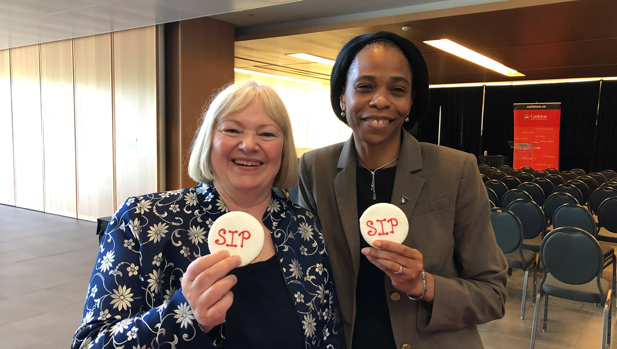"Lorraine Dyke and Patrice Smith hold cookies with ""SIP"" written on them in decorative frosting."