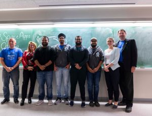 Carleton and Ottawa-area students pose together against a blackboard during Space Apps Ottawa 2019.