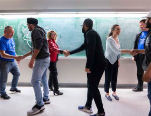 Carleton and Ottawa-area students shake hands near a blackboard during Space Apps Ottawa 2019.