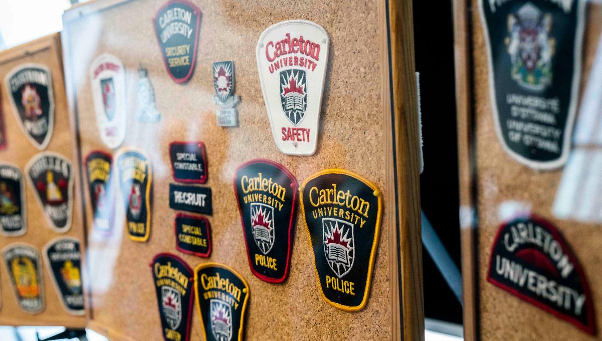 Various University Safety badges on display. An Ottawa police representative speaks at a podium. Carleton's special constables marked their 25th anniversary in Oct. 2018 with a celebration that recognized its partnership with the Ottawa Police Service.