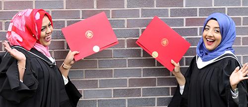 Two Carleton University graduates hold up their degrees