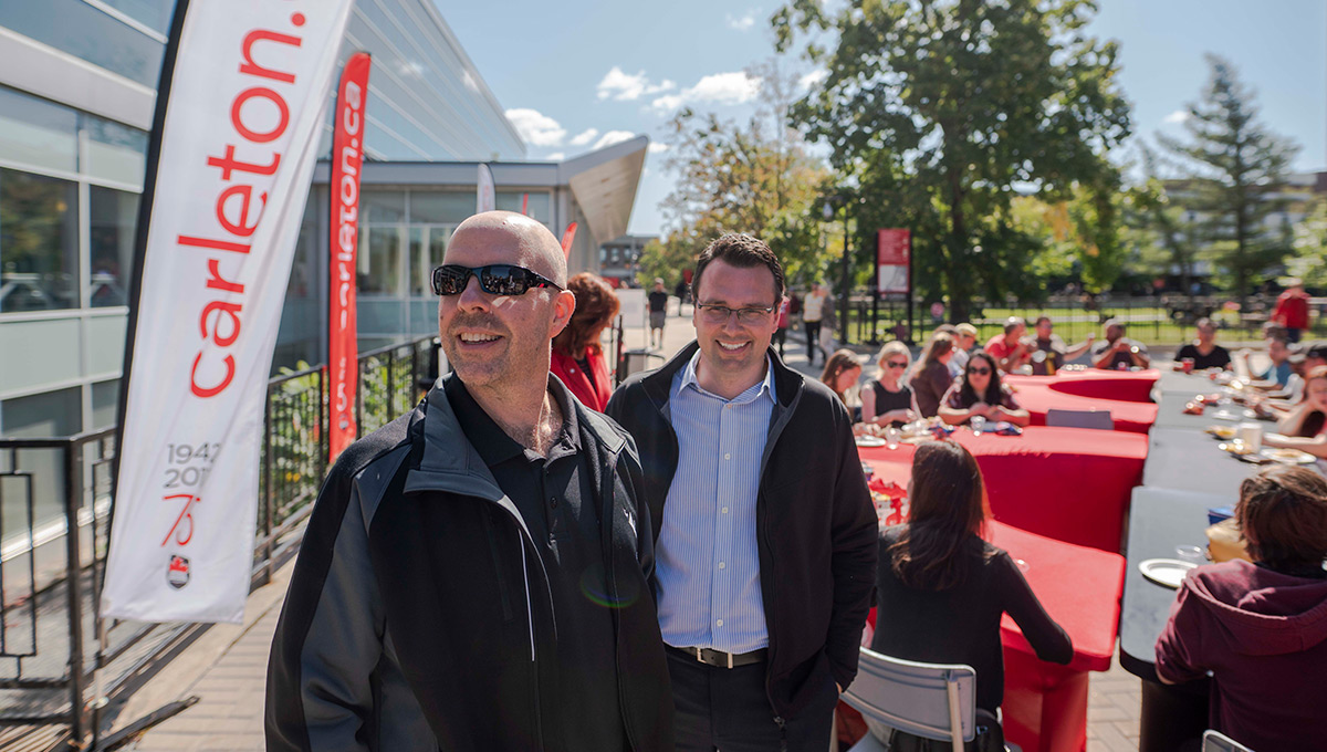 Carleton University President Benoit-Antoine Bacon and Mark Savenkoff, director of Alumni and Donor Relations, at the kickoff barbeque in the Tory Quad.