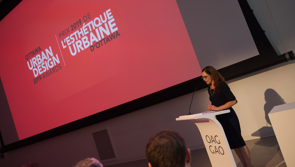 A speaker presents at a podium during the Urban Design Awards