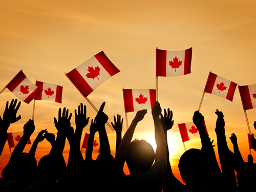 A crowd waves Canadian flags with the sunsetting in the background