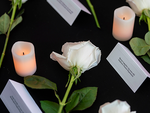 A white rose flanked by white candles