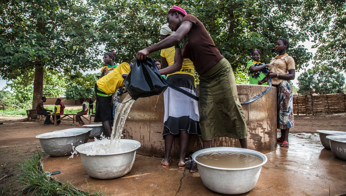 Several women collecting water in a well to the outside of the village of Fo Bouré, Benin.