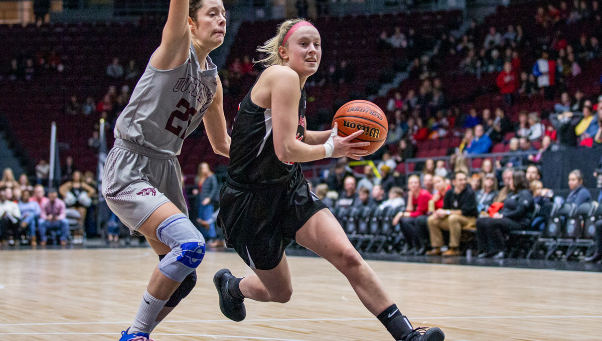 A Ravens women's basketball player goes to the basket against a uOttawa Gee Gees player.