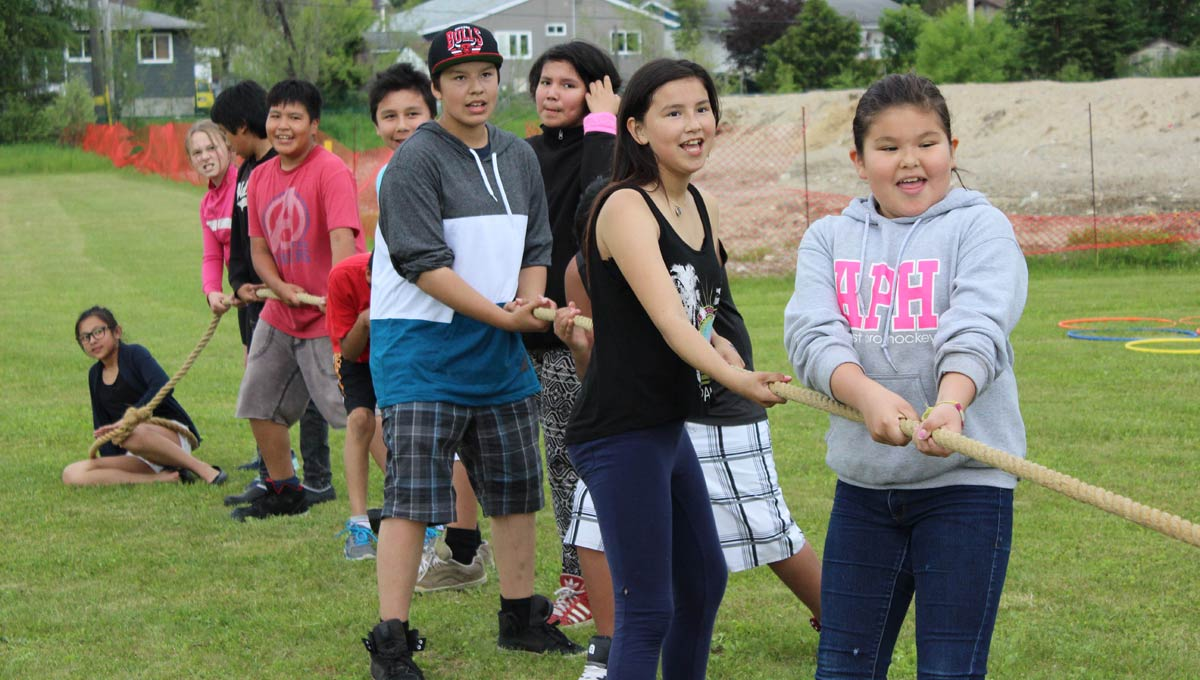 Indigenous Communities: Children and youth play tug of war outdoors.